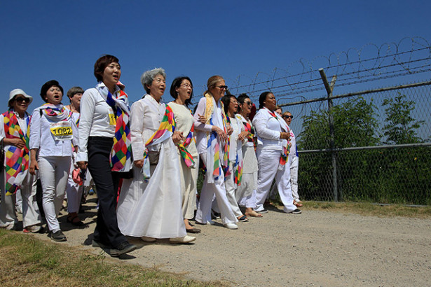 US activist Gloria Steinem (center) and Liberian Nobel Peace laureate Leymah Gbowee (right) march with other activists along the military wire fence near the border village of Panmunjom in Paju, South Korea, on May 24, 2015. (Photo: Chung Sung-Jun / Getty Images)