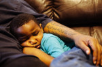 Troy Lowe, 4, sleeps under the arm of his father, Tory Lowe, in Milwaukee. Troy tested positive for lead poisoning after ingesting the tap water in their home. (Michael M. Santiago/News21)