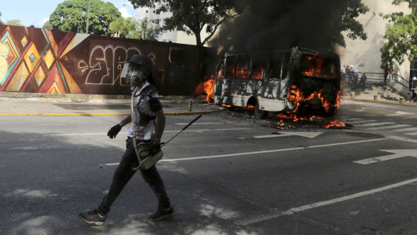 A protester wearing a gas mask and carrying a golf club walks to join fellow protesters, past a burning public transportation bus in Caracas, Venezuela, May 13, 2017. (AP/Fernando Llano)