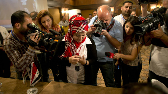 Firyal Sheikh El-Zour, 50, draws blood from her thumb with a syringe to use to mark a ballot, in Damascus, Syria, June 3, 2014. (AP/Dusan Vranic)