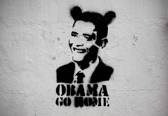 """An image of President Barack Obama wearing fake ears and the slogan """"Obama go home"""" on a street wall in Caracas, Venezuela. (AP/Ariana Cubillos)"""