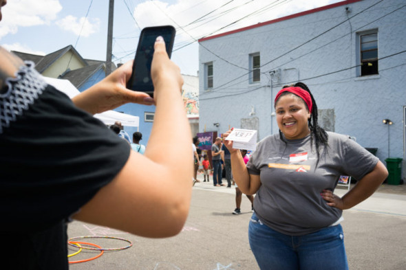 ABEP's intern Tatum Vanyo snaps photos of new pledges to Village Trust Financial Cooperative during the FLOW Northside festival. Photo by Annabelle Marcovici.