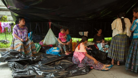Protesters sit under the plastic tent alongside the National Palace.