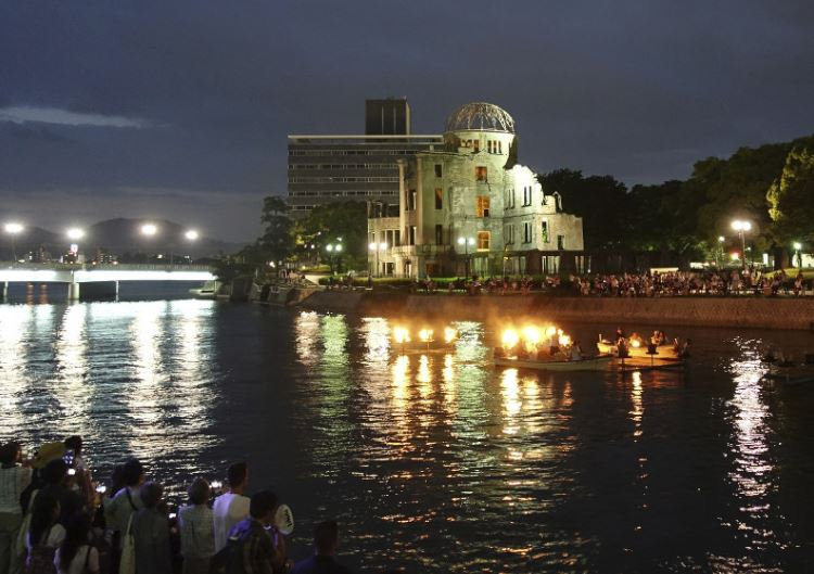 Aug. 5, 2017, photo, organizers of a peace prayer event light up torches on floats on the Motoyasu River next to the Atomic Bomb Dome in Hiroshima, western Japan, on the eve of the 72nd anniversary of the first U.S. atomic attack that killed 140,000 people in the city. (AP Photo/Mari Yamaguchi)