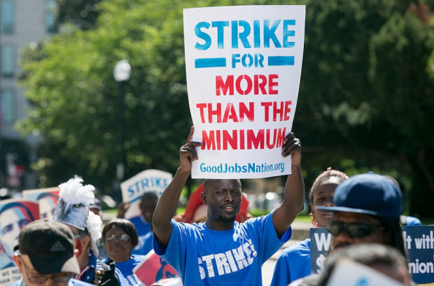 Protestors march in a rally on Capitol Hill in Washington to push for a raise to the federal minimum wage to $15 an hour, on July 22, 2015. (Photo By Al Drago/CQ Roll Call via Getty Images)
