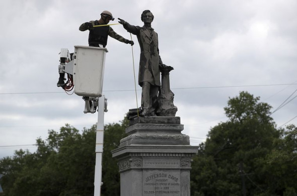 A New Orleans city worker wears body armor and a face covering as he measures the Jefferson Davis monument in May in New Orleans, six days before its removal. Source: Justin Sullivan/Getty Images