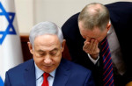 Israeli Prime Minister Benjamin Netanyahu listens to an adviser at the start of the weekly cabinet meeting at his office in Jerusalem onAugust 6 [Reuters/Gali Tibbonl]