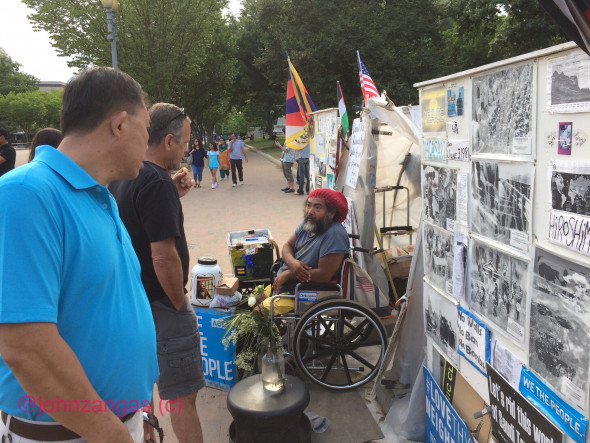 Visitors approach the Peace Vigil and talk with Melaku-Bello about war, politics, and social justice. Photo: John Zangas