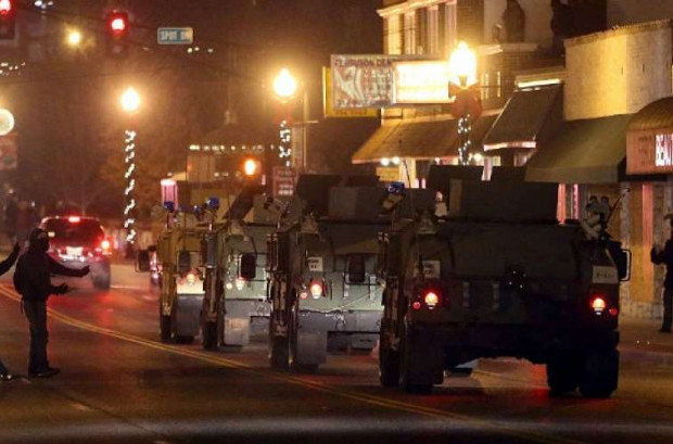 Protestors confront a convoy of Missouri National Guard humvees as they drive near the Ferguson police station on November 25, 2014 in Ferguson, Missouri. (Photo: Justin Sullivan/Getty Images)