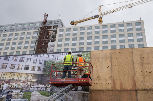 Two men work on construction of a future housing and shopping complex near 8th and Market streets in June 2016. (Jessica Christian/S.F. Examiner)