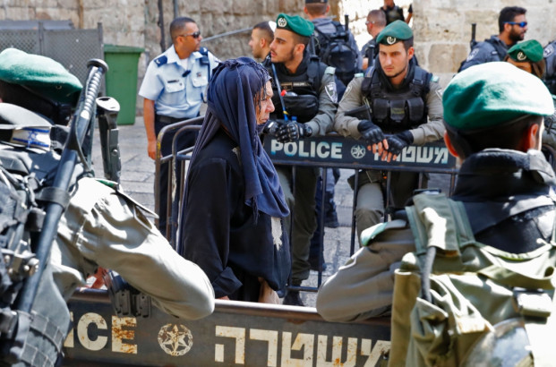 Jack Guez/AFP/Getty Images. A Palestinian Muslim woman heading to pray at the Al Aqsa Mosque compound in Jerusalem's Old City walks past Israeli security forces on July 28, 2017.