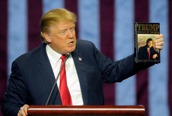 "Republican presidential candidate Donald Trump holds up a copy of his book ""The Art of the Deal,"" given to him by a fan as he speaks during a campaign stop on Saturday, Nov. 21, 2015 in Birmingham, Ala. Eric Schultz/AP"