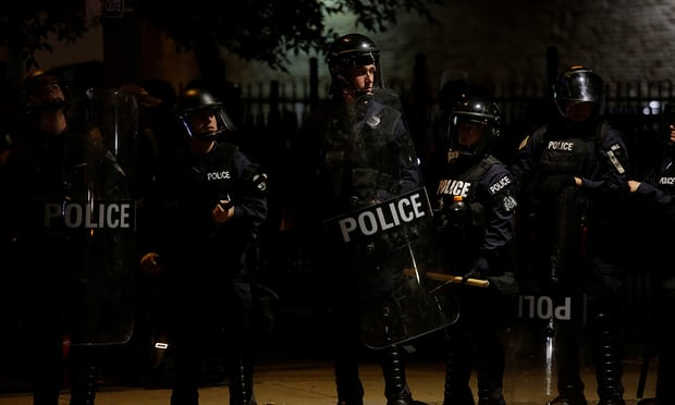 Police officers watch demonstrators on Sunday night after Jason Stockley, a former St Louis police officer, was found not guilty of the murder of Anthony Lamar Smith in 2011. Photograph: Joshua Lott/Reuters