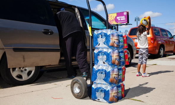 A volunteer loads bottles of water into the car of a family whose water has been shut off. Photograph: Garrett MacLean for the Guardian