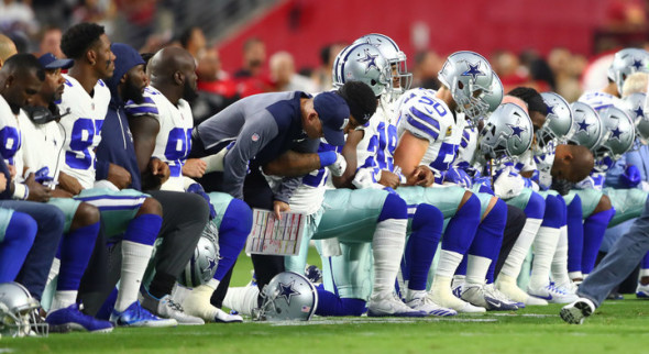 USA TODAY SPORTS / REUTERS Dallas Cowboys players kneel together with their arms locked prior to the game against the Arizona Cardinals at University of Phoenix Stadium on Monday.