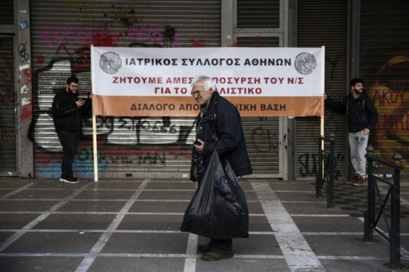 "A man stands in front of a banner during an anti-austerity rally by workers in the health sector outside the Labour ministry in Athens, March 2, 2017. The banner reads : ""Medical Association of Athens, We demand the immediate withdraw of the pension bill"". (AP/Yorgos Karahalis)"
