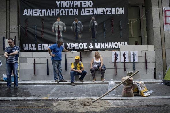 "Protesting hospital staff sit in front of a wall that they built at the entrance of the Greek Finance Ministry with a banner depicting Greek Prime Minister Alexis Thipras , Deputy Health Minister Pavlos Polakis and Greek Finance Minister Euclid Tsakalotos wearing ties reading in Greek ""Ministry of broken promises"" and "" We drown in debt and bailouts"" in central Athens, June 16, 2017. (AP/Petros Giannakouris)"