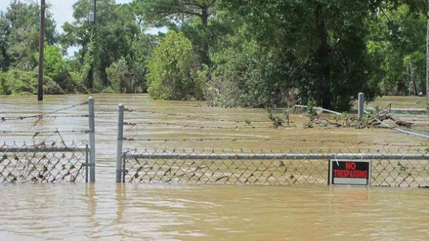 In this Aug. 31, 2017 file photo, a barbed-wire fence encircles the Highlands Acid Pit that was flooded by water from the nearby San Jacinto River as a result from Harvey. (AP Photo/Jason Dearen)
