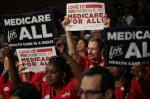 Supporters of the Medicare for All Act of 2017 hold signs at an event to introduce the bill in Washington, DC. Photo by Alex Wong / Getty Images.