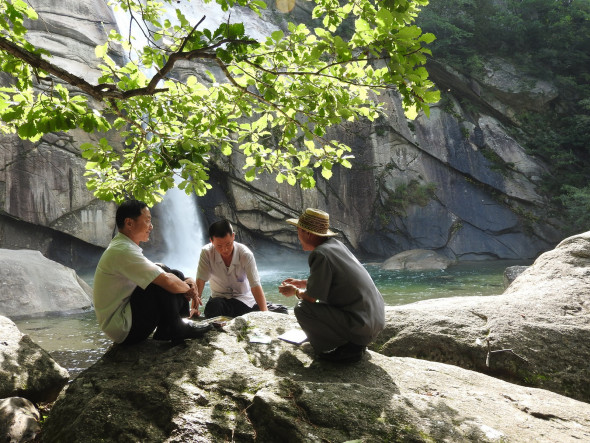 A group of men sit and chat near the base of the waterfall.