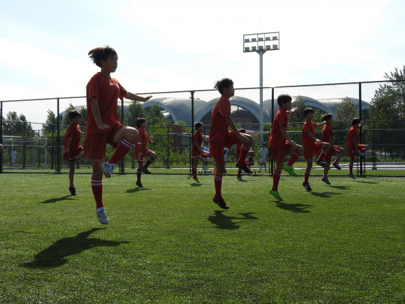 The Pyongyang International Football School opened in 2013. The complex includes a massive stadium and a school teaching all subjects, with football as a focus for the roughly 200 students. Different classes practiced their skills outside, doing warm-up drills to energetic music. When years ago I lived in Korea's south, practicing Tae Kwan Do I warmed-up to similar drills.
