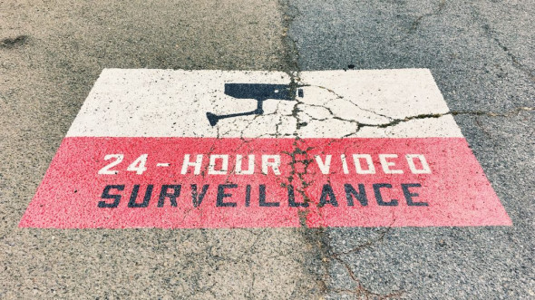 "A stencil painted on the ground reads ""24-Hour Video Surveillance."" (Flickr / throgers, CC NC ND license)"