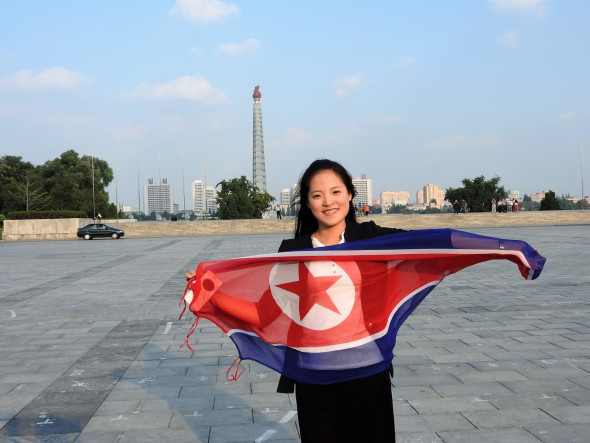 "One of our hosts, Kim-Young, holding the flag of the DPRK. Behind her, the Juche tower, so-named after the dominant philosophy of self-reliance. Our other host, Kim Song-Nam, explained: ""The Juche philosophy was created by President Kim Il-Sung. Man decides his own destiny, we rely on our own resources."""