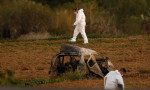 Forensic experts walk in a field after a powerful bomb blew up a car killing investigative journalist Daphne Caruana Galizia. Photograph: Darrin Zammit Lupi/Reuters