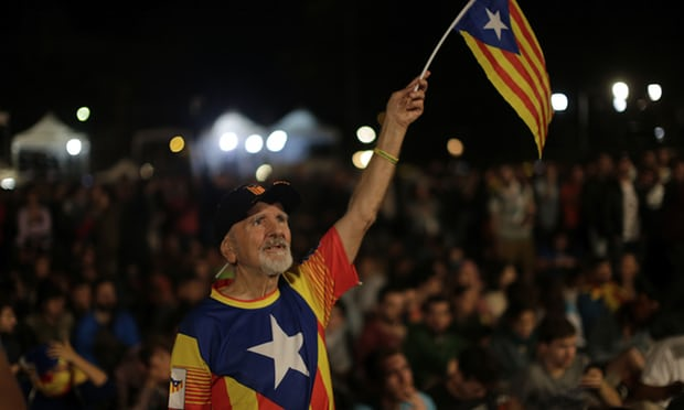 A man waves an estelada, or Catalonia independence flag, during a gathering at Plaza Catalonia in Barcelona on the day of the referendum. Photograph: Emilio Morenatti/AP
