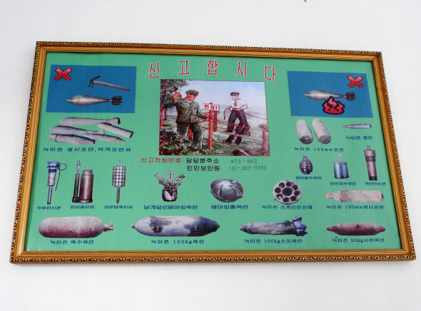 "In a hallway in the Middle School, a poster encourages students to alert authorities if they come across unexploded ordnance (UXOs). Our host, Kim Song-Nam, said: ""We're still discovering old bombs, for example when we dig to lay the foundation for a building."" This article noted the discovery of nearly 400 UXOs near an elementary school playground, that farmers periodically come across UXOs, and that the cleanup period may take longer than 100 years. At the Pyongyang War Museum, we learned: ""There were 400,000 people in Pyongyang, and they dropped more bombs than that on the city."" 428,000 bombs, according to the museum guide."