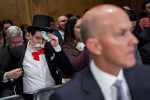 BLOOMBERG VIA GETTY IMAGES A demonstrator sits in costume behind Richard Smith, former chairman and chief executive officer of Equifax Inc., right, before a Senate Banking Committee hearing in Washington, D.C., on Wednesday, Oct. 4, 2017.
