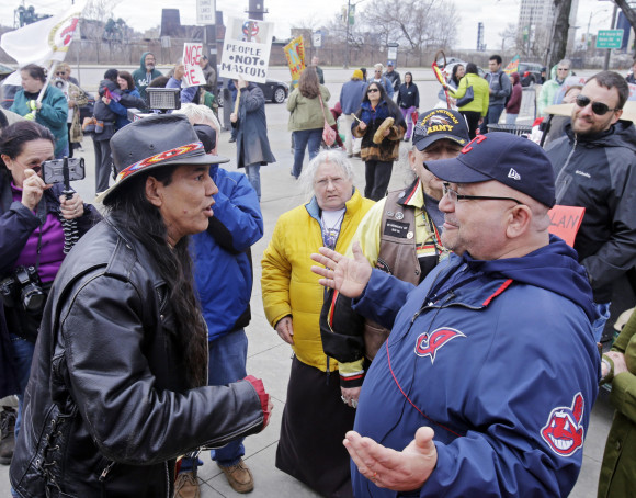 Indian protester confronts  Philip Yenyo, Executive Director of the American Indian Movement, Ohio, pictured left; unidentified Cleveland fan, right.