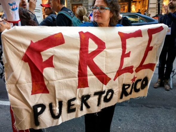A protester holds a sign in support of Puerto Rican independence. (WNV/Ashoka Jegroo)