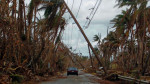 A car drives under tilted power line poles in the aftermath of Hurricane Maria in Humacao, Puerto Rico, Oct. 2, 2017.