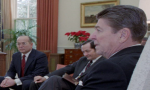 """Walter Raymond Jr. was the CIA propaganda and disinformation specialist who oversaw """"political action"""" and """"psychological operations"""" projects at the National Security Council in the 1980s. Raymond is seated next to National Security Adviser John Poindexter/Photo: Reagan presidential library"""