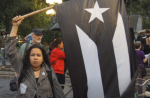 A woman holds a black Puerto Rican flag during a rally in Union Square this October. Credit: Dean Patterson.