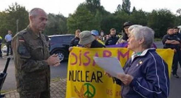 Sister Ardeth Platte on July 17 hands a copy of the newly adopted United Nations Treaty on the Prohibition of Nuclear Weapons to Gregor Schlemmer, commander of Büchel Air Base in Germany, a deployment site for 20 US nuclear-armed B61 H-bombs. Sister Carol Gilbert is in the brown hat. Photo by Marion Kuepker