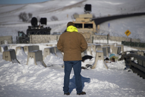 An activist stands in silent protest by a police barricade near Oceti Sakowin Camp on the edge of the Standing Rock Sioux Reservation on Dec. 4, 2016, outside Cannon Ball, N.D. Photo: Jim Watson/AFP/Getty Images
