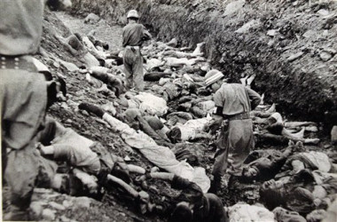 """In this July 1950 U.S. Army file photograph once classified """"top secret,"""" South Korean soldiers walk among some of the thousands of South Korean political prisoners shot at Taejon, South Korea, early in the Korean War. (AP Photo/National Archives, Major Abbott/U.S. Army, File)"""