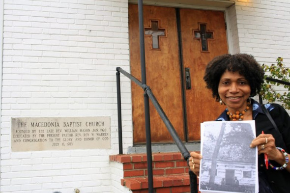 Marsha Coleman-Adebayo holds up a photo taken in 1895 of the home of Pascal Botts, which was located near the Macedonia church. Local historians have recently helped piece together the story of the community. Credit: Andrew Bossone