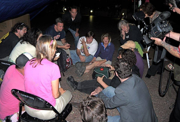 Bill Moyer, left with black t shirt and glasses on his head, and other core October2011 team members strategize during the early days of the occupation.
