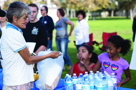 Kathy Cline accepts food and water from a food-sharing event in El Cajon's Wells Park.
