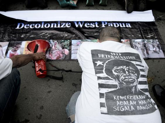 An Indonesian activist kneels before West Papuan pro-independence demonstrators in a symbolic gesture seeking forgiveness for their country's occupation during a protest in Jakarta in April (Getty)