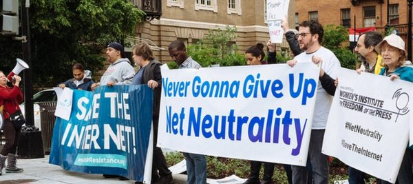 never going to give up net neutrality. protesters outside of ajit pai speech. e1519431092775