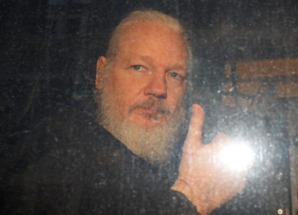 assange shows thumbs up after being arrested. e1555258624139