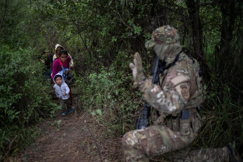 us military at border confronts migrant family. reuters.