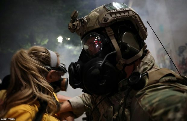 federal troop pushes a mother back during a demonstration against the presence of trumps federal cops. reuters e1595780665293