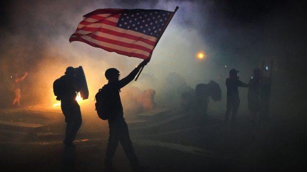 portland protester enveloped in tear gas hold american flag. e1595781541158